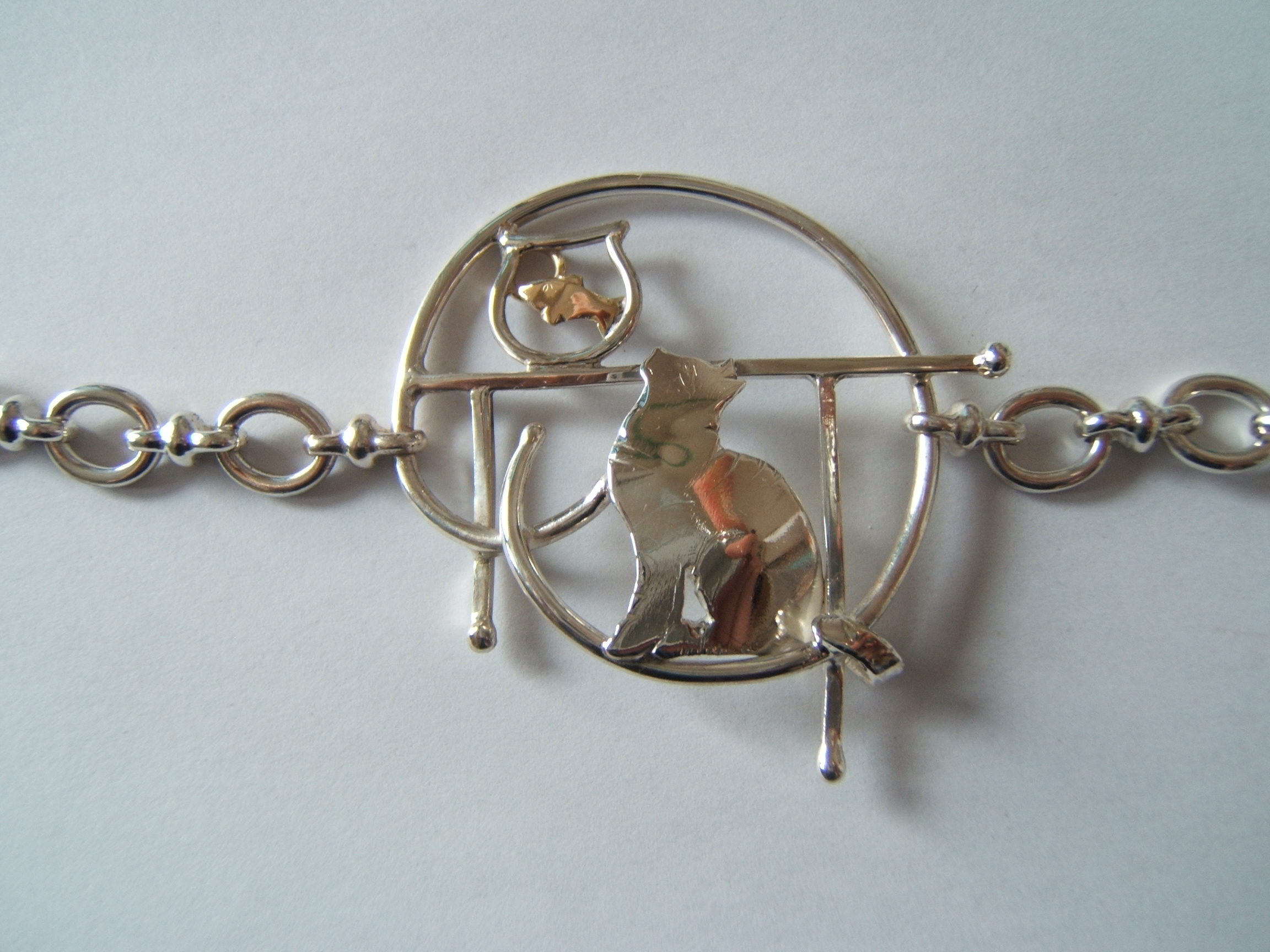 silver cat and a goldfish bracelet by helen burrell