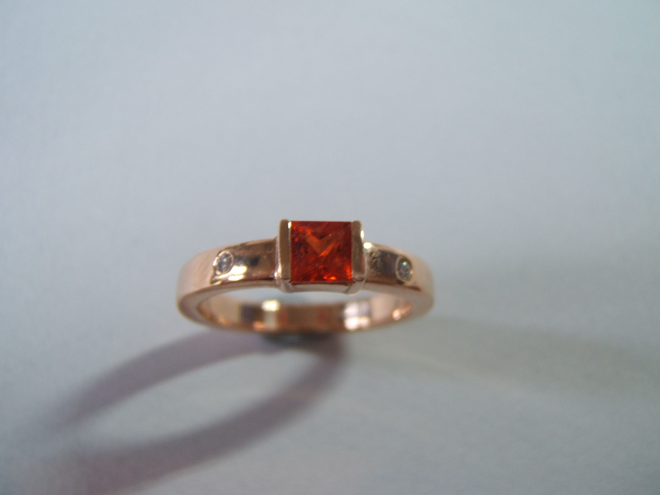 the simple ring set with an orange sapphire in 9ct rose gold