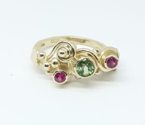 <img src='9 carat gold ring by helen burrellset with a beautiful green tourmaline and two pink sapphires 'alt=green tourmaline and pink sapphire ring'>